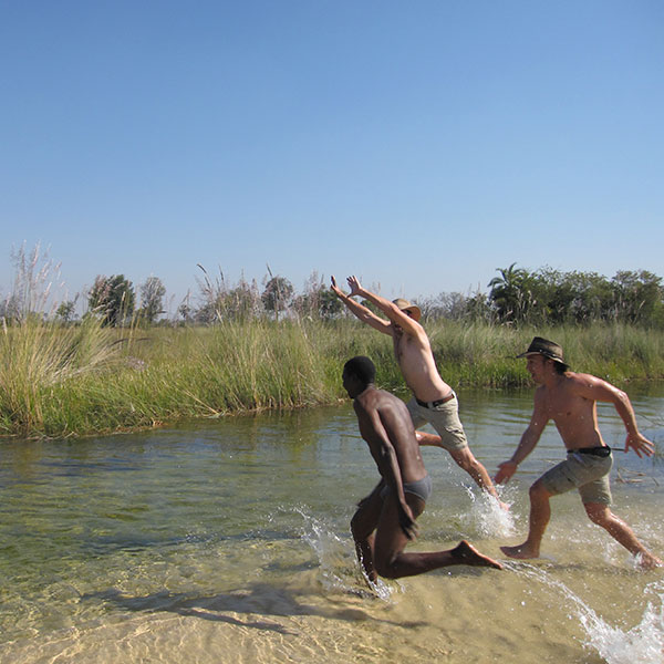 Three men playfully running into the crystal clear waters of the Okavango Delta
