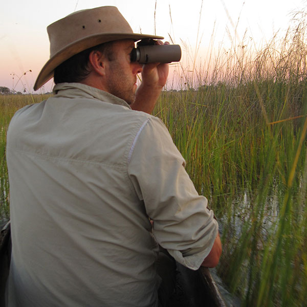 A man wearing a safari hat sits in a mokoro on the Okavango Delta and looks through a pair of Swarovski binoculars