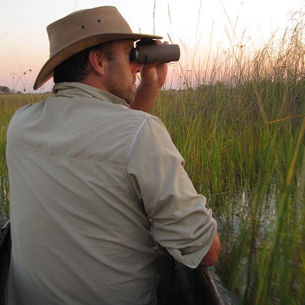 A man wearing a safari hat sits in a mokoro on the Okavango Delta and looks through a pair of Swarovski binoculars