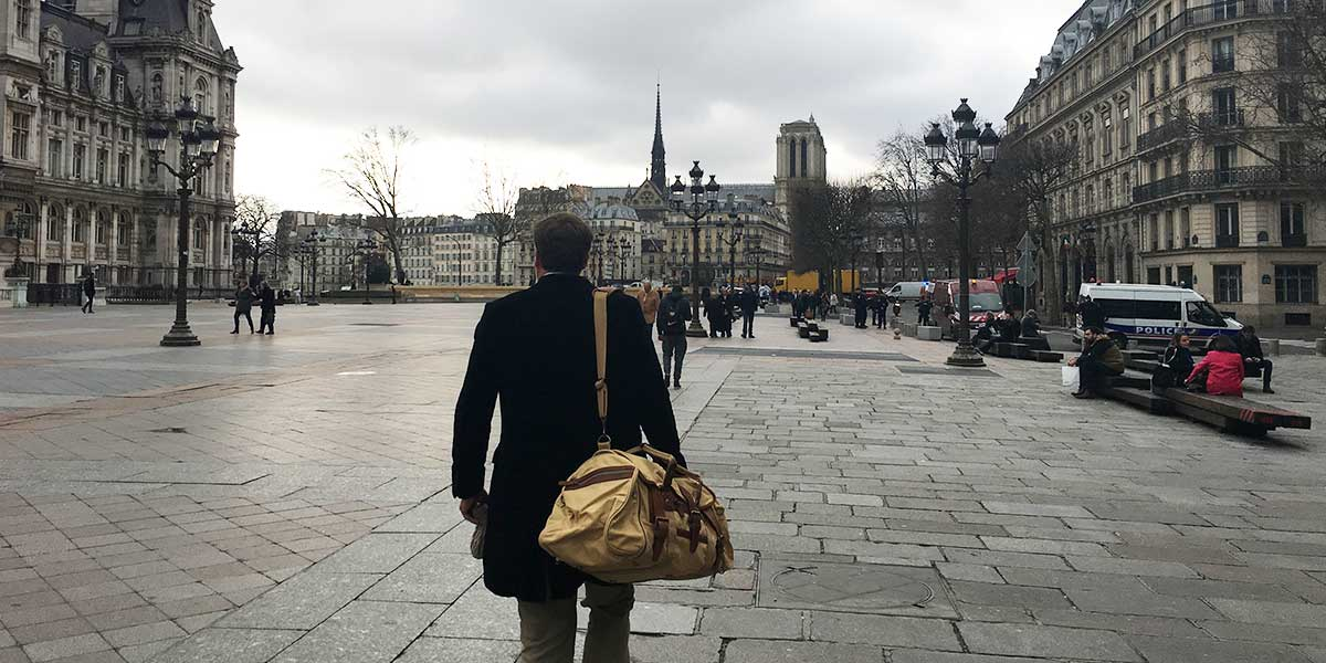A man in a coat walking in Paris, France, with a view of the Eiffel tower in the background