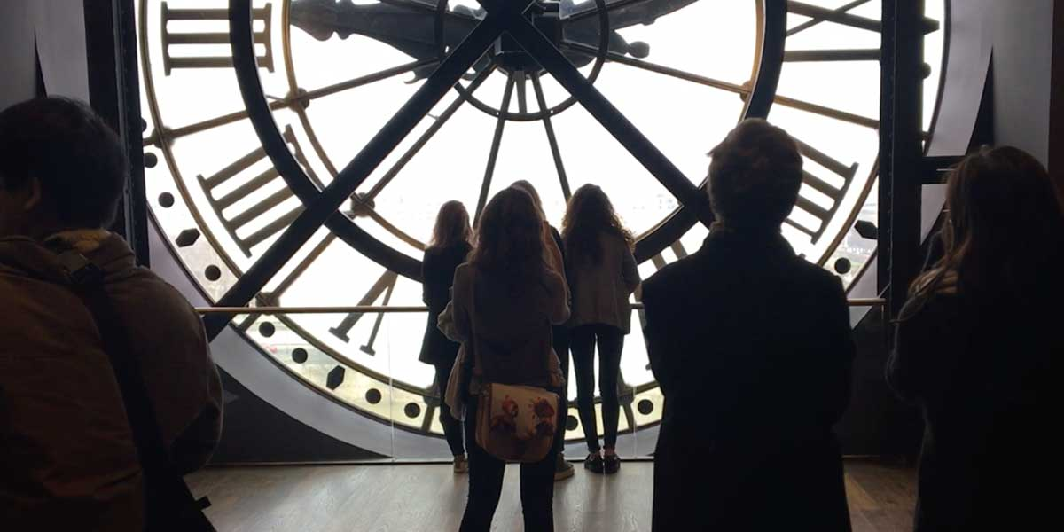 A woman standing behind a large clock in Paris, France