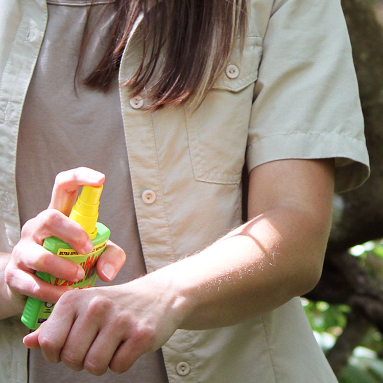 Woman applying insect repellent
