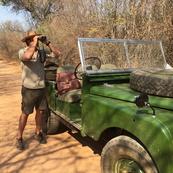 Man (Steve) with Land Rover looking through binoculars, Safari Store