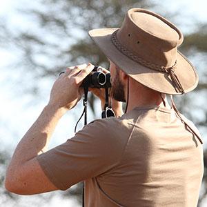 A man on safari looking through a pair of binoculars
