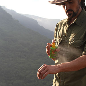 A man spraying insect repellent on his arm