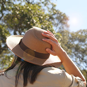 A woman on safari wearing a wide-brimmed hat