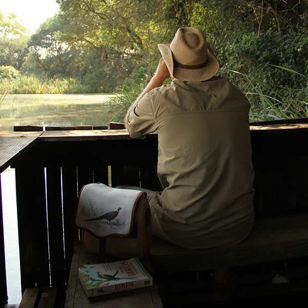 A man sitting in a bird hide looking through a pair of binoculars with a bird book and satchel at his side