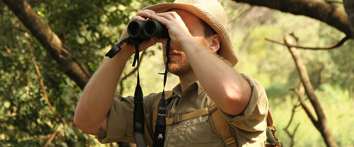 A man on safari carrying a canvas backpack looks through a pair of binoculars