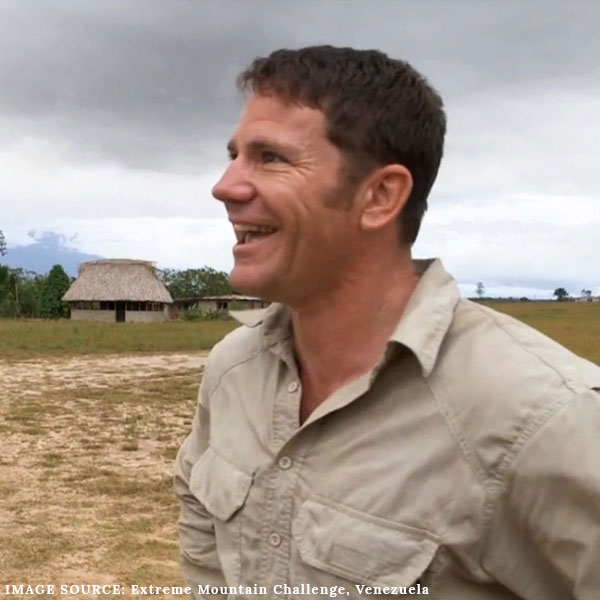 Steve Backshall smiling and wearing a safari outdoor shirt on BBC's Extreme Mountain Challenge with a hut in the background