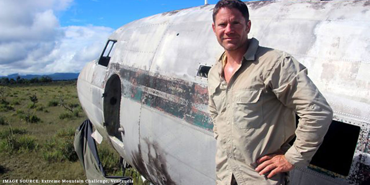 Steve Backshall standing in front of an airplane in Venezuela for BBC's Extreme Mountain Challenge wearing an outdoor shirt