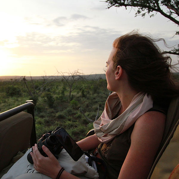 A woman wearing a scarf sitting in the back of a safari vehicle in Thanda, holding a pair of Swarovski binoculars with an iPhone attached