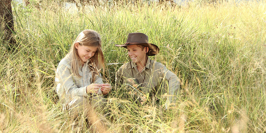 A smilling boy and girl sitting in tall grass on safari