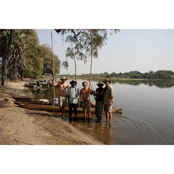 Five smiling men holding wooden poles stand next to mokoros on the bank of the Okavango Delta river in Botswana.