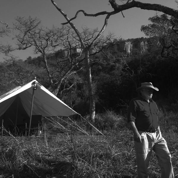 Man wearing safari clothing on safari walking away from tent in Africa.