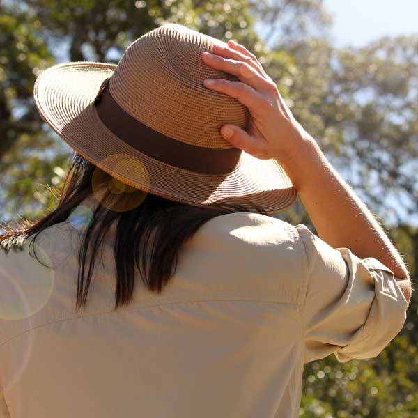 A woman wearing a wide-brimmed hat looks up at the sky.