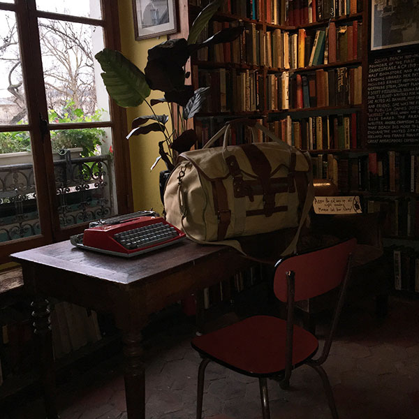 A canvas and leather duffle bag on a desk in an old library in Paris, France