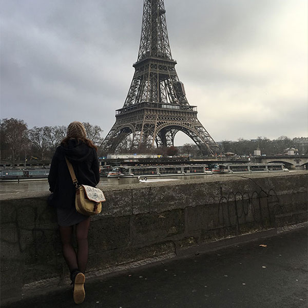 A woman carrying a satchel looks out at the Eiffel Tower in Paris, France
