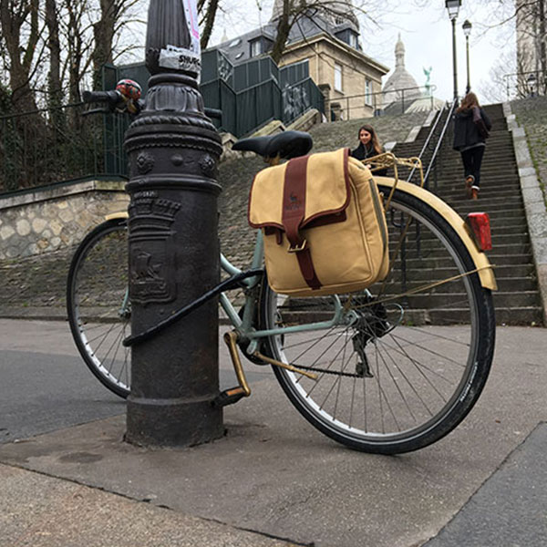 A bicycle with a canvas and leather pannier bag is parked on a street in Paris, France