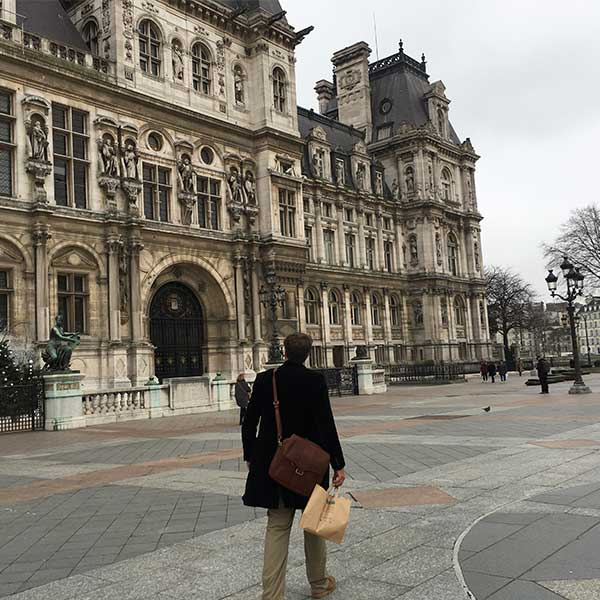 A man carrying a leather pannier bag walks the streets of Paris, France
