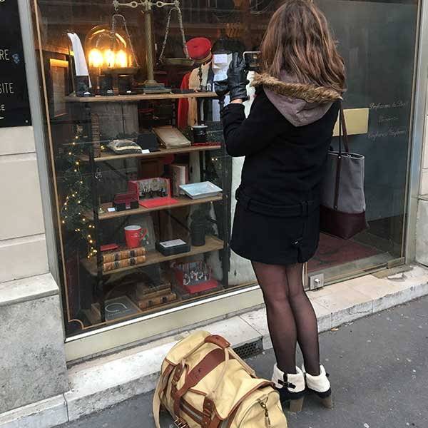 A woman looking through a shop window in Paris, France