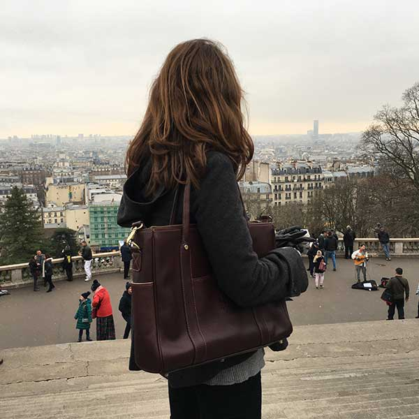 A woman holding a leather business bag in Paris, France