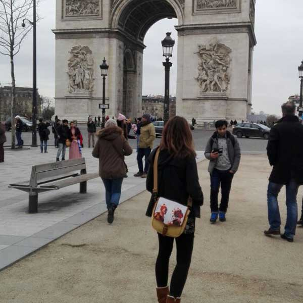A woman standing in front of the Arc de Triomphe in Paris, France