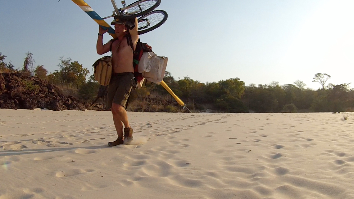 A shirtless man walks in the sand next to the Zambezi river in Zambia carrying a sail, a bicycle and some luggage.