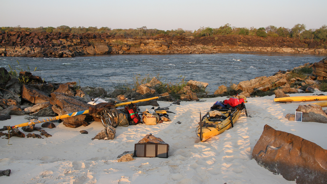 Camping next to the Zambezi river. Bicycles, luggage, a Hobie, a sun panel and other gear is lying in the white sand.