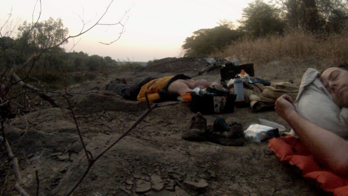 Two men sleep on a river bank next to the Zambezi. They are surrounded by shoes, luggage and other safari gear.