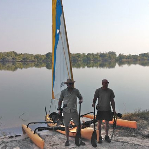 Two men wearing safari clothing and sunglasses stand next to the Zambezi river with their Hobie and oars.
